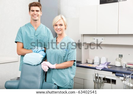 Portrait of a confident male and female dentists smiling at dental clinic - stock photo