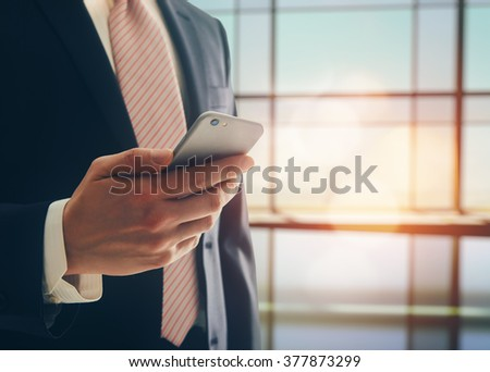 Portrait of a confident man. Entrepreneur working on phone while standing in modern office interior. Intelligent male lawyer holding phone. - stock photo