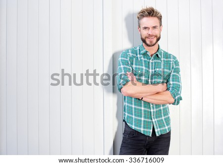 Portrait of a confident man with beard smiling against white background - stock photo