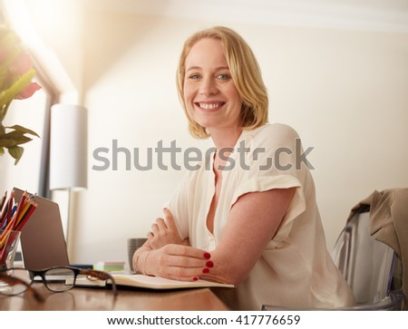 Portrait of a confident mature woman sitting at working desk. Happy businesswoman working from home.