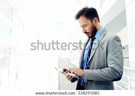 Portrait of a confident men entrepreneur dressed in expensive suit working on digital tablet while standing in modern office interior, intelligent male lawyer working on touch pad during work break  - stock photo