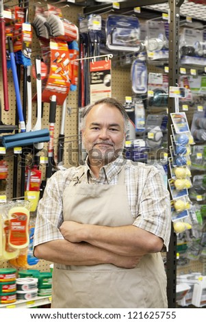 Portrait of a confident middle-aged store clerk with arms crossed in hardware shop