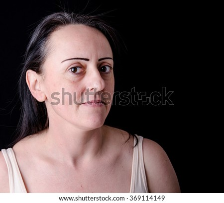 Portrait of a confident middle aged woman. Black background with copy space. - stock photo