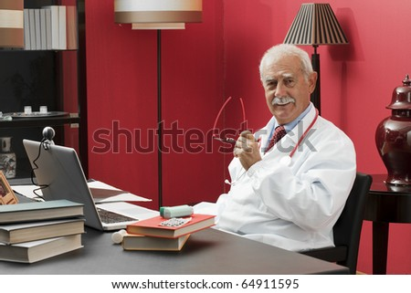 Portrait of a confident senior doctor smiling at camera - stock photo