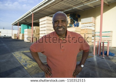 Portrait of a confident senior man with hands akimbo at warehouse - stock photo