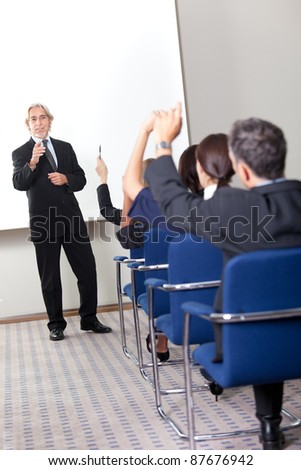 Portrait of a confident senior manager giving presentation to his colleagues at office - stock photo