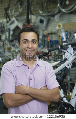 Portrait of a confident shop keeper with arms crossed standing in a shop