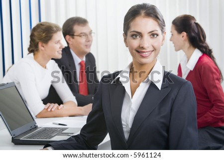 Portrait of a confident woman with her business team on the background