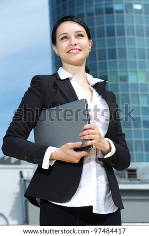 Portrait of a confident young business lady against downtown background. - stock photo