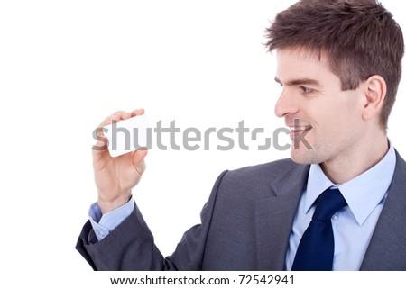 Portrait of a confident young business man looking at his  business card against white background - stock photo