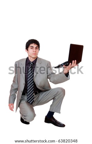 Portrait of a confident young business man standing with laptop against white background