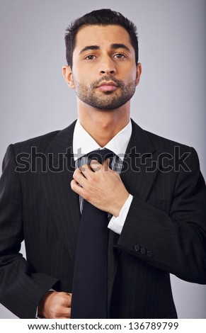 Portrait of a confident young businessman fixing his necktie - stock photo
