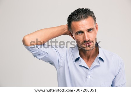 Portrait of a confident young businessman standing in shirt isolated on a white background. Looking at camera - stock photo