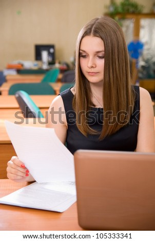 Portrait of a confident young businesswoman working on  paper at office - stock photo