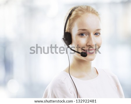 Portrait of a confident young female customer service agent with headset isolated over white background - stock photo