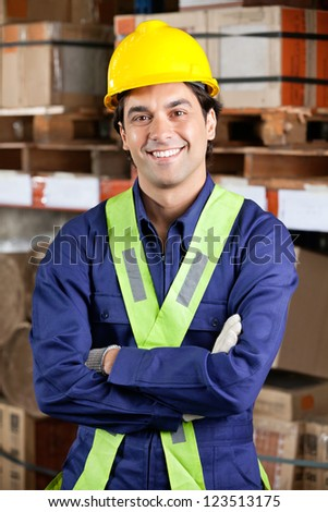 Portrait of a confident young foreman in uniform with arms crossed at warehouse - stock photo