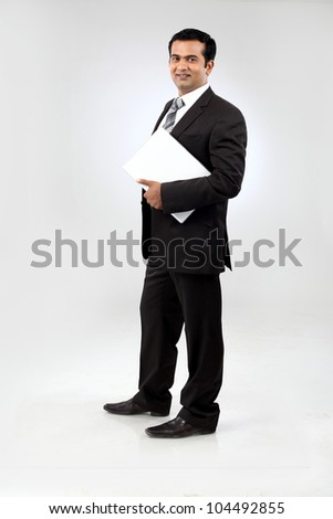 Portrait of a confident young indian business man standing with laptop - stock photo