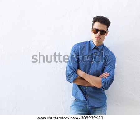 Portrait of a confident young man posing with sunglasses standing against white background - stock photo