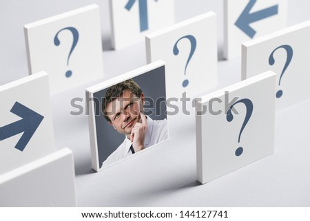 Portrait of a confused businessman surrounded by question marks and arrows - stock photo