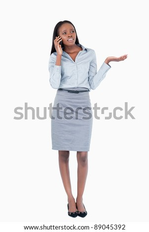 Portrait of a confused businesswoman making a phone call against a white background - stock photo