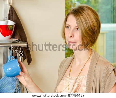 Portrait of a confused female standing and holding a cap in the kitchen