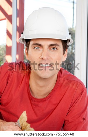 Portrait of a construction worker with paint brushes and white hard hat - stock photo