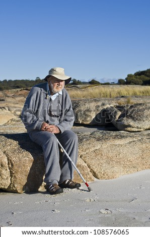 Portrait of a contemplative attractive senior man in his nineties, holding walking stick sitting down on rocks at beach watching the sea. - stock photo