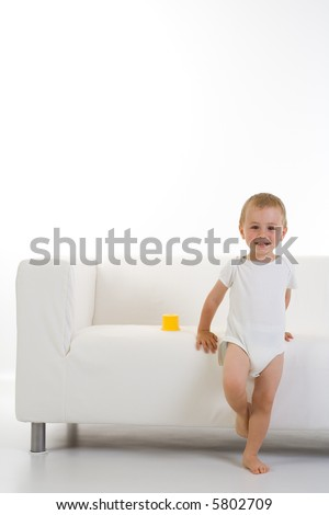 Portrait of a content young child in one piece white clothing, standing leaning against a white couch/sofa in a room with white floor and walls. - stock photo