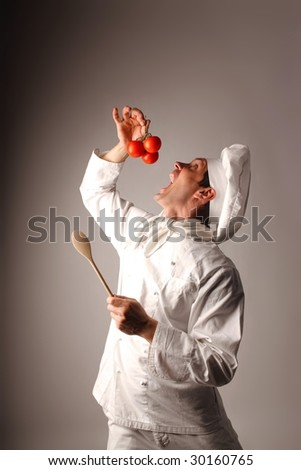 portrait of a cook eating tomato - stock photo