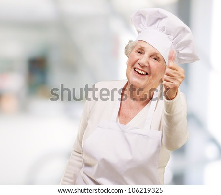portrait of a cook senior woman doing a good gesture indoor