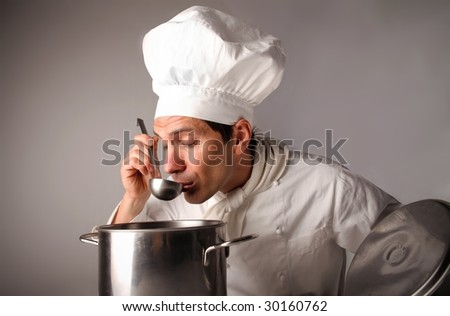 portrait of a cook tasting a soup in a pot - stock photo