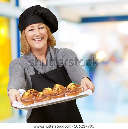 portrait of a cook woman showing a homemade muffins tray at a restaurant - stock photo