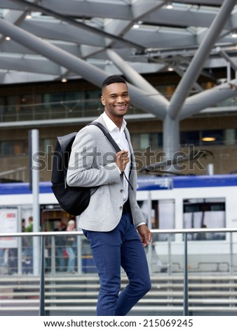 Portrait of a cool guy smiling with bag at station - stock photo