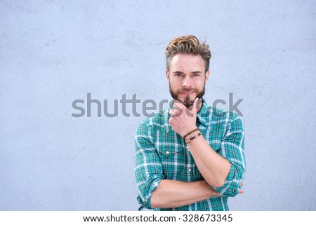 Portrait of a cool guy smiling with hand on chin - stock photo