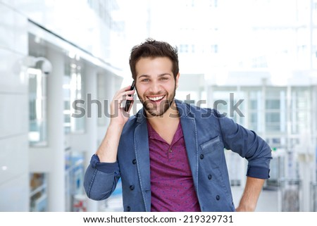 Portrait of a cool guy smiling with mobile phone - stock photo