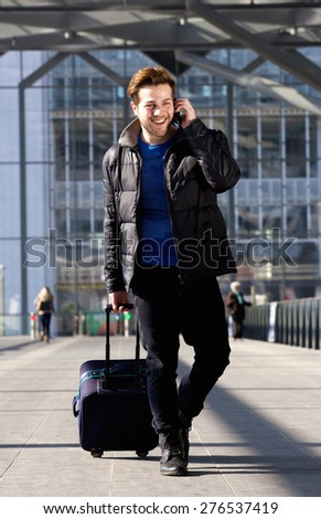 Portrait of a cool guy walking with mobile phone and bag at station - stock photo
