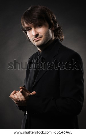Portrait of a cool man against black background - stock photo