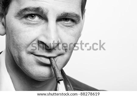 portrait of a cool mature man smoking a cigar - stock photo