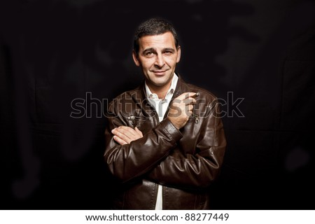 portrait of a cool mature man with leather jacket over black background - stock photo
