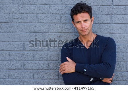 Portrait of a cool older man with arms crossed against gray wall - stock photo