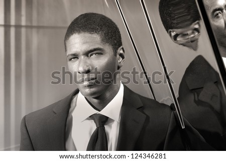 Portrait of a cool young businessman in modern setting in suit and tie - stock photo
