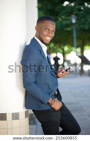 Portrait of a cool young businessman sending text message by mobile phone - stock photo