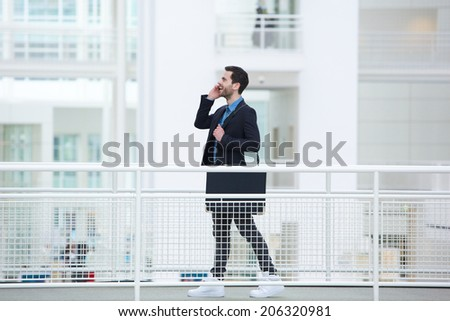 Portrait of a cool young businessman talking on mobile phone - stock photo