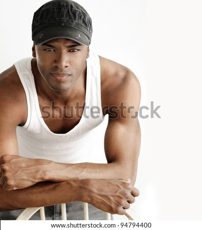 Portrait of a cool young man leaning on chair in white tank and trendy cap against neutral background - stock photo