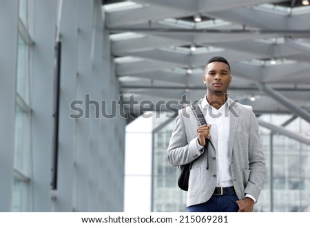 Portrait of a cool young man walking inside station building with bag - stock photo