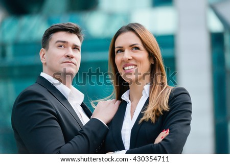 Portrait of a corporate business man and business woman, standing in front of office building - stock photo