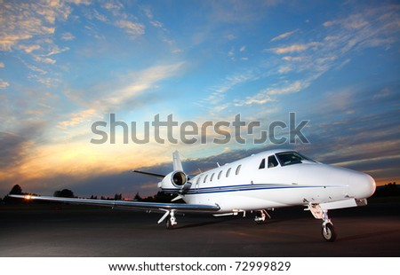 Portrait of a corporate jet on the runway against an evening sky. - stock photo
