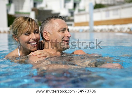 Portrait of a couple bathing in a swimming pool - stock photo