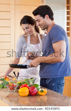 Portrait of a couple cooking with a pan in their kitchen - stock photo