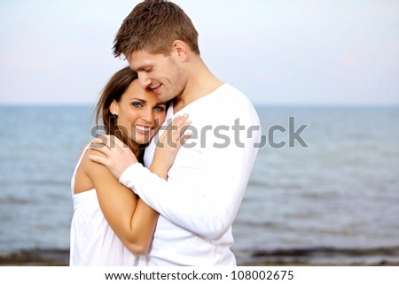 Portrait of a couple cuddling at the beach looking happy - stock photo